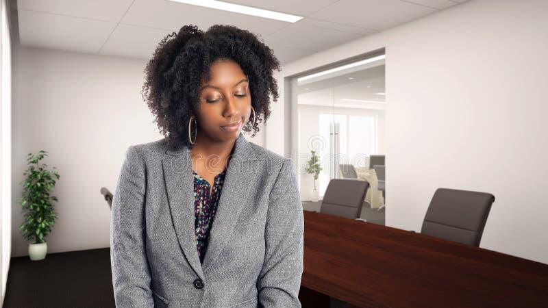 Femme d'affaires In d'afro-américain un bureau semblant timide ou embarrassé photographie stock