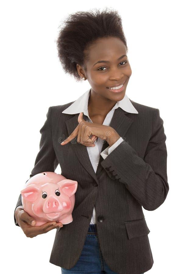 Femme d'affaires afro-américaine d'isolement avec la tirelire : argent concentré photo libre de droits