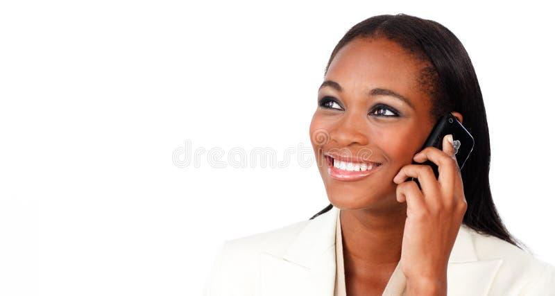 Femme d'affaires afro-américaine rougeoyante au téléphone photo stock