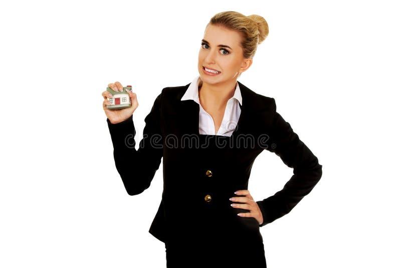 Femme d'affaires agressive écrasant la petite maison photographie stock