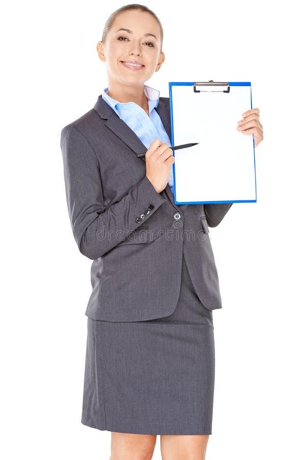 Femme d'affaires amicale indiquant un presse-papiers photo libre de droits