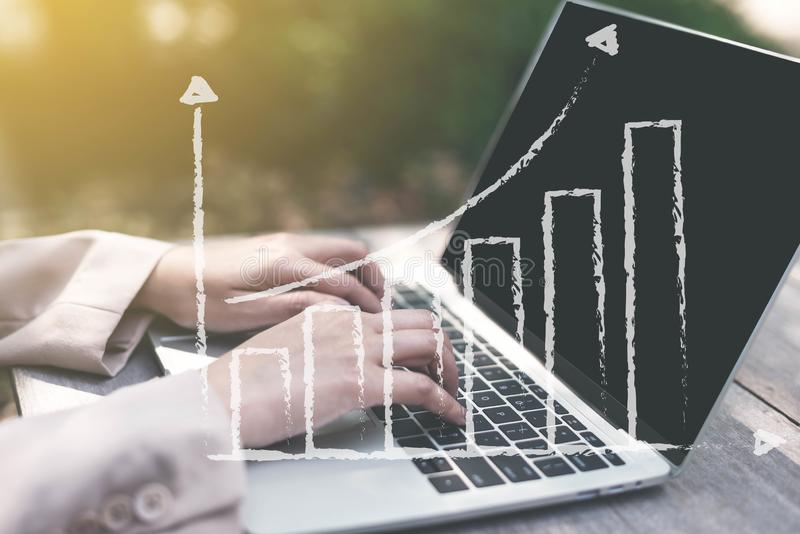 Femme d'affaires analysant des statistiques avec l'écran d'ordinateur portable, fonctionnant avec les diagrammes financiers de gr images libres de droits