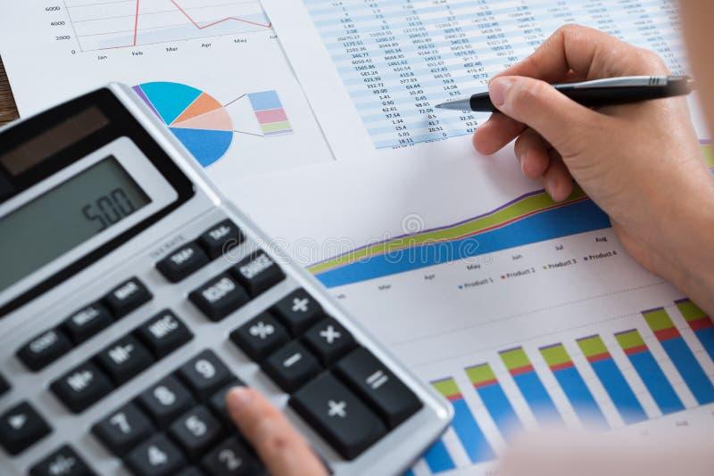 Femme d'affaires Analyzing Financial Report avec la calculatrice image stock