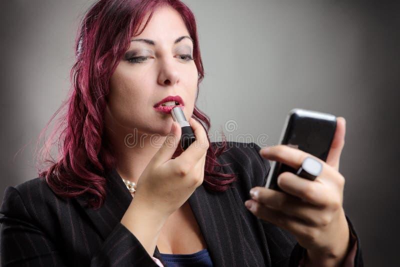 Femme d'affaires appliquant le maquillage photographie stock libre de droits