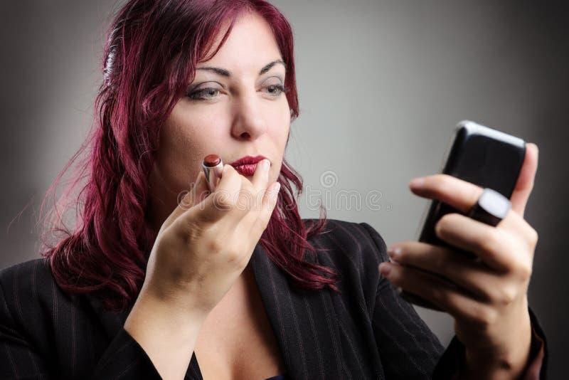 Femme d'affaires appliquant le maquillage photos stock