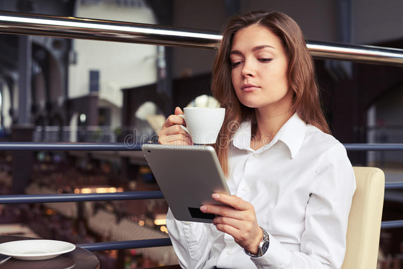 Femme d'affaires appréciant la tasse de café aromatique et lisant des lates image stock