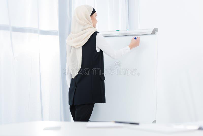 femme d'affaires arabe faisant des notes sur le conseil blanc photographie stock
