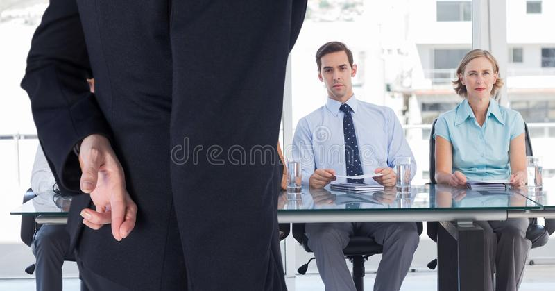 Femme d'affaires arrivant à une entrevue avec ses doigts croisés images libres de droits