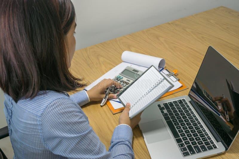 Femme d'affaires asiatique calculer le nombre financier sur le rapport images stock