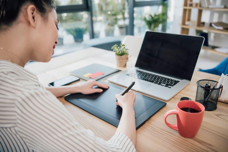 Femme d'affaires asiatique de sourire à l'aide du comprimé graphique à la table avec l'ordinateur portable image stock