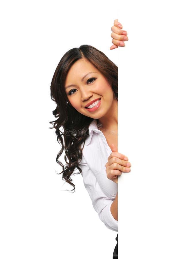 Femme d'affaires asiatique magnifique retenant le signe blanc images stock