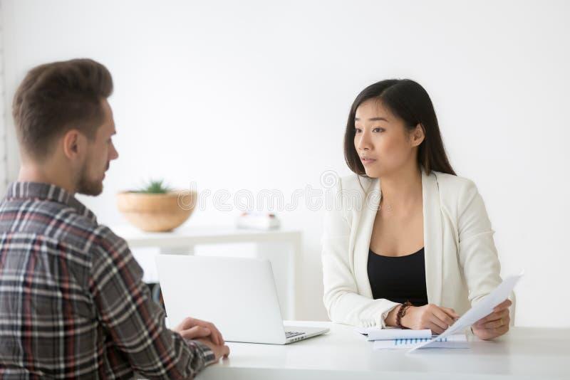 Femme d'affaires asiatique sérieuse méfiante discutant le docu d'affaires photo stock
