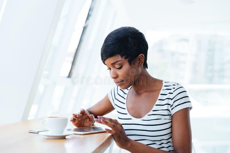 Femme d'affaires assez africaine employant l'amd de comprimé ayant la pause-café images libres de droits