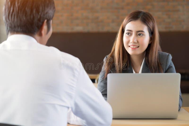 Femme d'affaires assistant à écouter un client à qui parle photographie stock