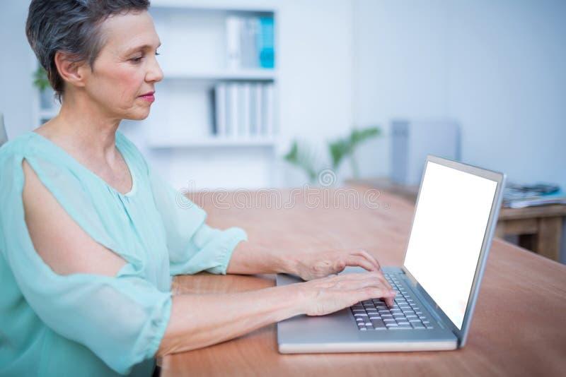 Download Femme D'affaires Attentive Travaillant Sur L'ordinateur Portable Photo stock - Image du occasionnel, cahier: 56484330