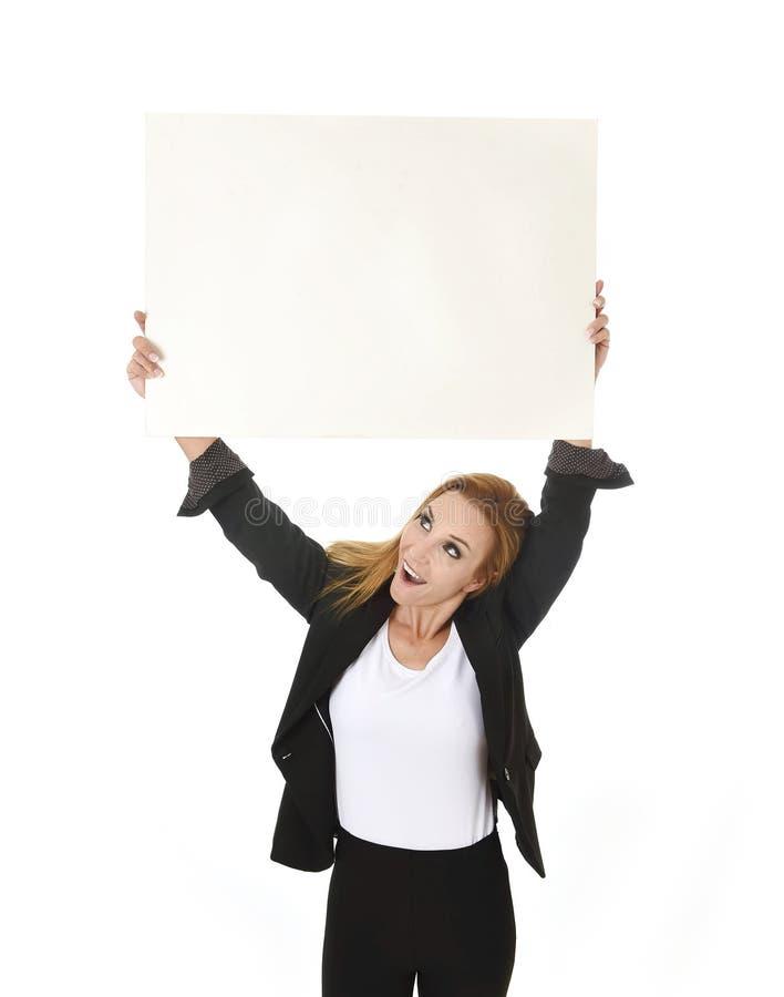 Femme d'affaires attirante de portrait de la publicité jugeant le panneau d'affichage vide avec le sourire de l'espace de copie h images libres de droits