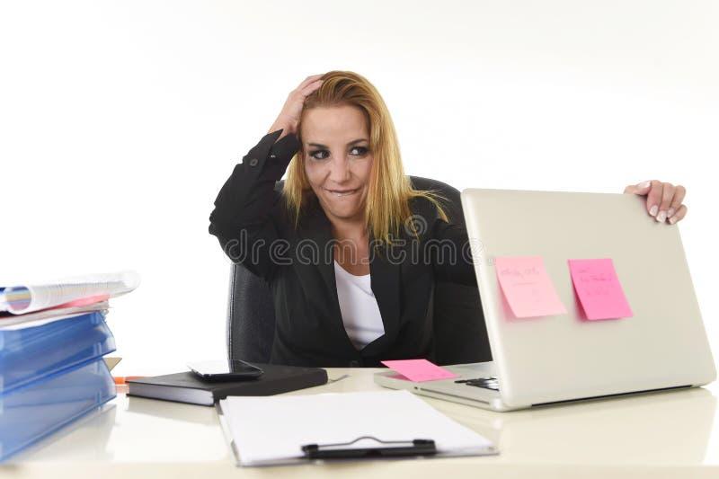 Femme d'affaires attirante inquiétée dans l'effort fonctionnant avec l'ordinateur portable au bureau accablé et surmené image libre de droits