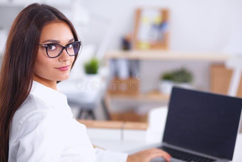 Femme d'affaires attirante s'asseyant sur le bureau dans photographie stock libre de droits