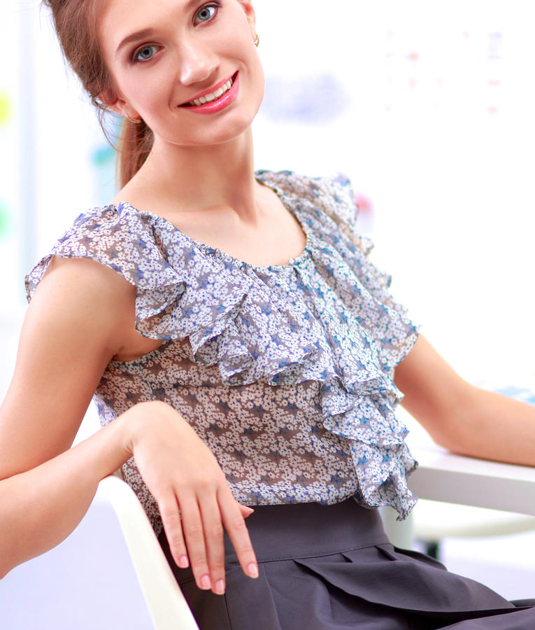 Femme d'affaires attirante s'asseyant sur le bureau dans le bureau image libre de droits