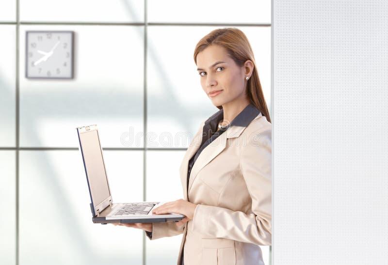Femme d'affaires attirante utilisant le sourire d'ordinateur portatif images libres de droits