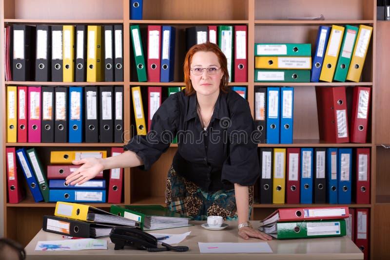 Femme d'affaires au bureau dirigeant la main sur la pile de reliures photo stock