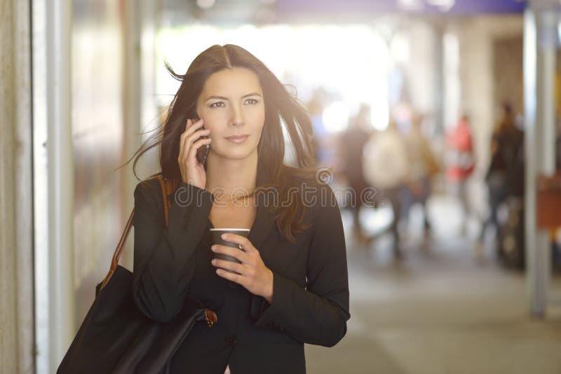 Femme d'affaires au téléphone marchant dans le mail images stock