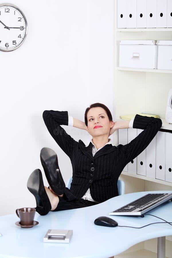 Femme d'affaires avec des pattes s'étendant sur le bureau images libres de droits