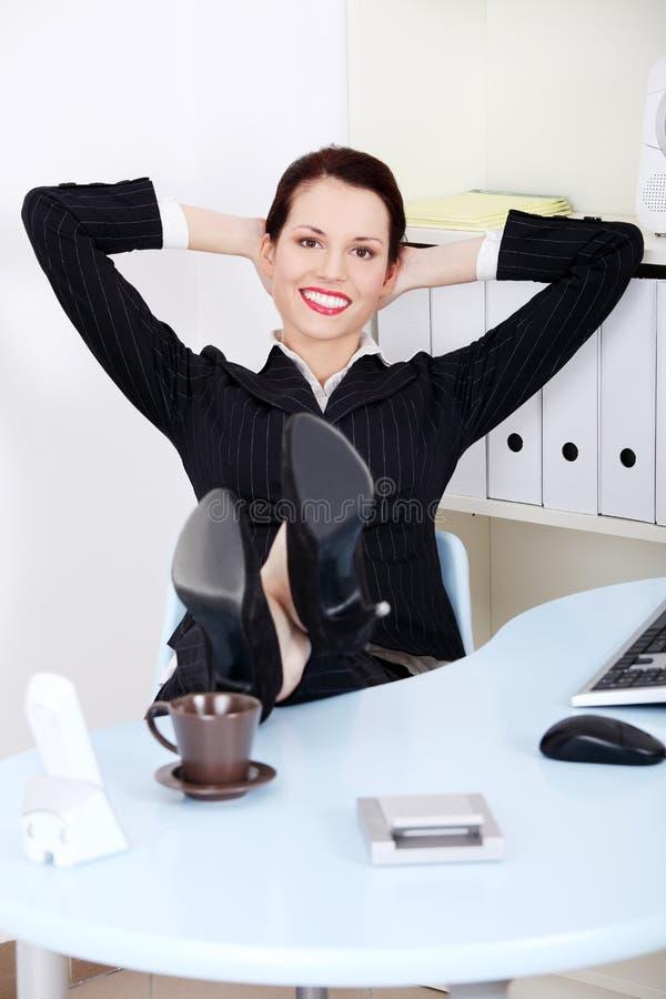 Femme d'affaires avec des pattes s'étendant sur le bureau photographie stock