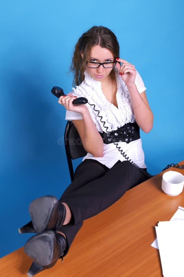 Femme d'affaires avec des pattes sur le bureau images stock