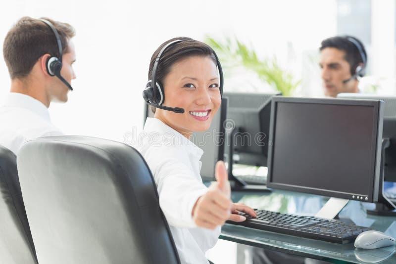 Femme d'affaires avec des tumbs regardant l'appareil-photo tandis que son travailler de collègues images libres de droits