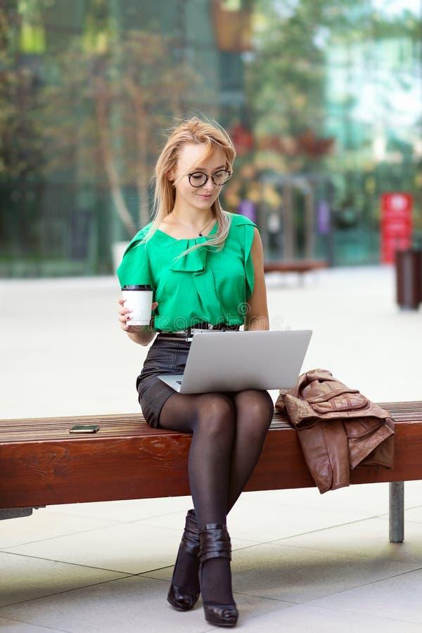 Femme d'affaires avec des verres se reposant sur le banc en dehors du café potable de district des affaires de parc de rue et tra photos libres de droits