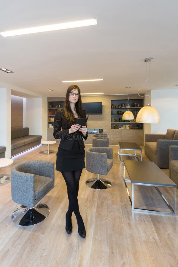 Femme d'affaires avec des verres se tenant dans le bureau image libre de droits