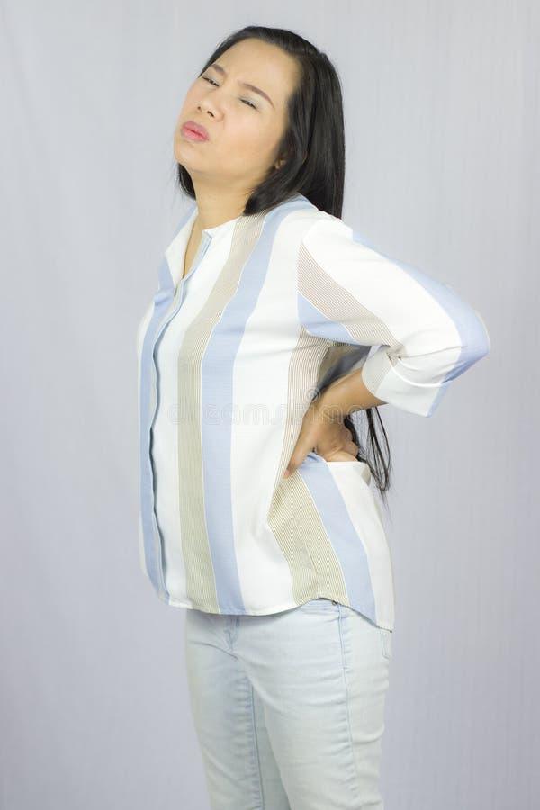 Femme d'affaires avec douleurs de dos, souffrant des douleurs de dos d'isolement sur le fond gris photo stock