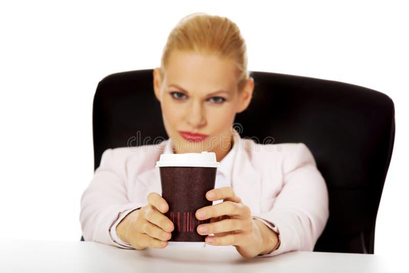 Femme d'affaires avec du café dans la tasse de papier se reposant derrière le bureau image libre de droits