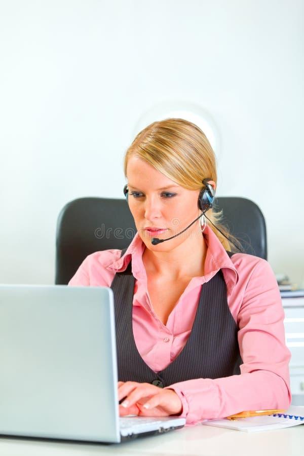 Femme d'affaires avec l'écouteur travaillant sur l'ordinateur portatif photos stock