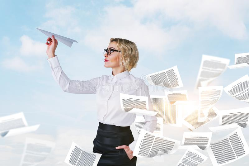 Femme d'affaires avec l'avion de papier, surcharge de documents photos stock