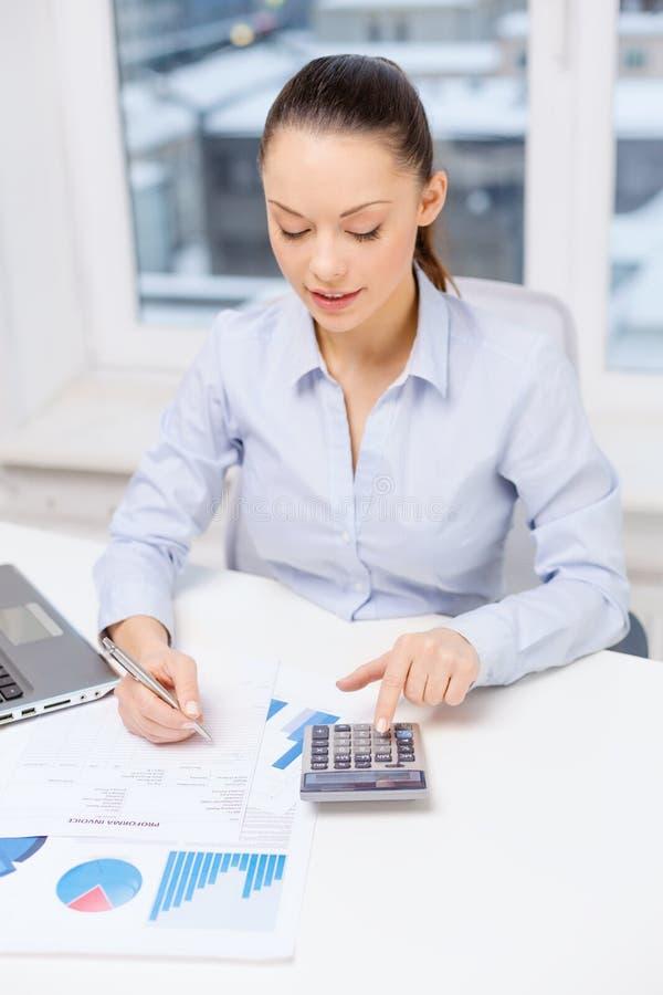 Femme d'affaires avec l'ordinateur portable et diagrammes dans le bureau photos stock