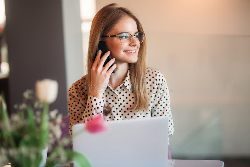 Femme d'affaires avec l'ordinateur portable et le téléphone en café Travailler heureux de jeune fille image libre de droits