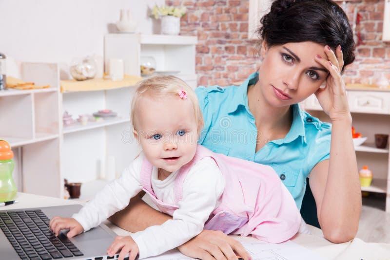 Femme d'affaires avec l'ordinateur portable et son bébé photographie stock