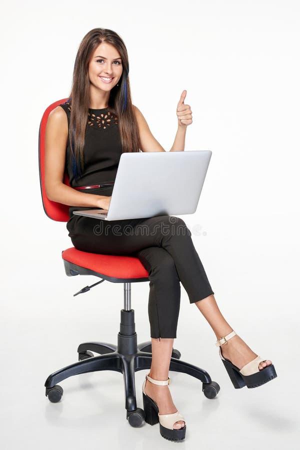 Femme d'affaires avec l'ordinateur portable faisant des gestes le pouce  photographie stock libre de droits