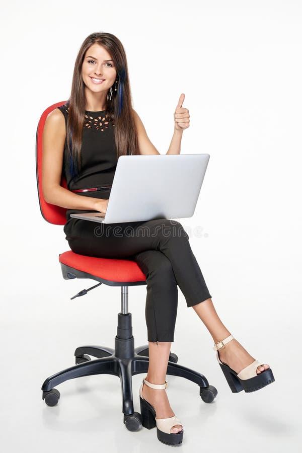 Femme d'affaires avec l'ordinateur portable faisant des gestes le pouce  images libres de droits