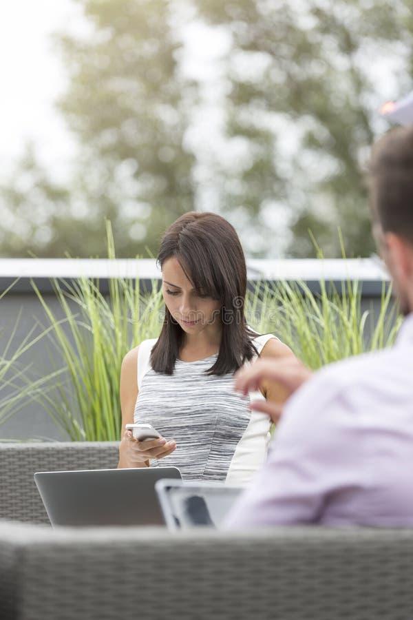 Femme d'affaires avec l'ordinateur portable utilisant le smartphone par le collègue à la terrasse de bureau images libres de droits