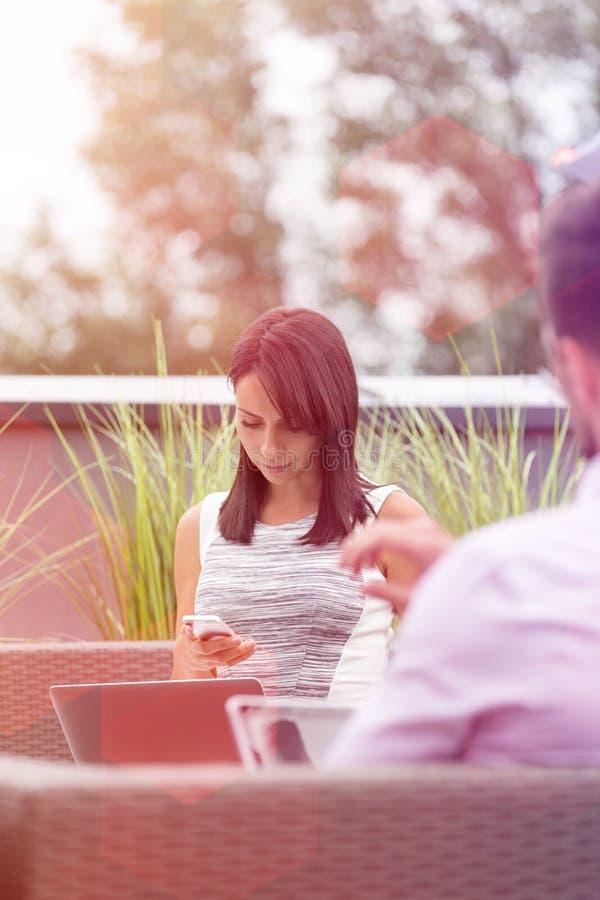 Femme d'affaires avec l'ordinateur portable utilisant le smartphone par le coll?gue ? la terrasse de bureau photo libre de droits
