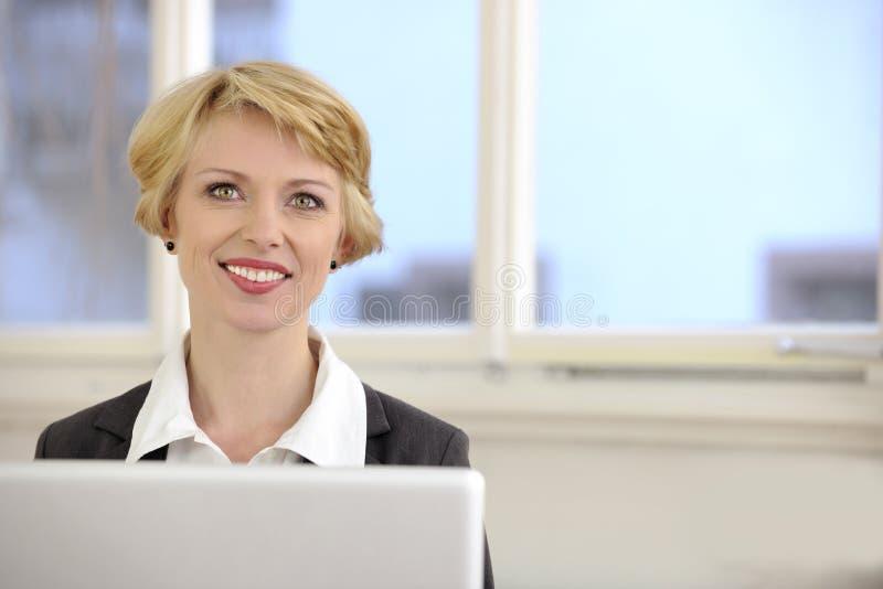 Femme d'affaires avec l'ordinateur portatif photo stock