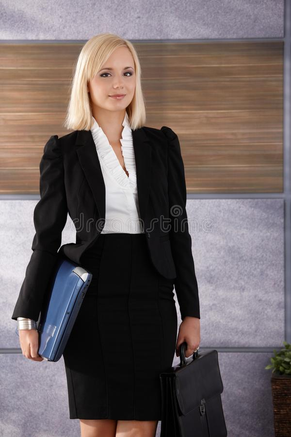 Femme d'affaires avec l'ordinateur portatif et la serviette photographie stock libre de droits