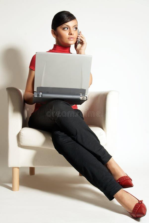 Femme d'affaires avec l'ordinateur portatif et le téléphone photographie stock libre de droits