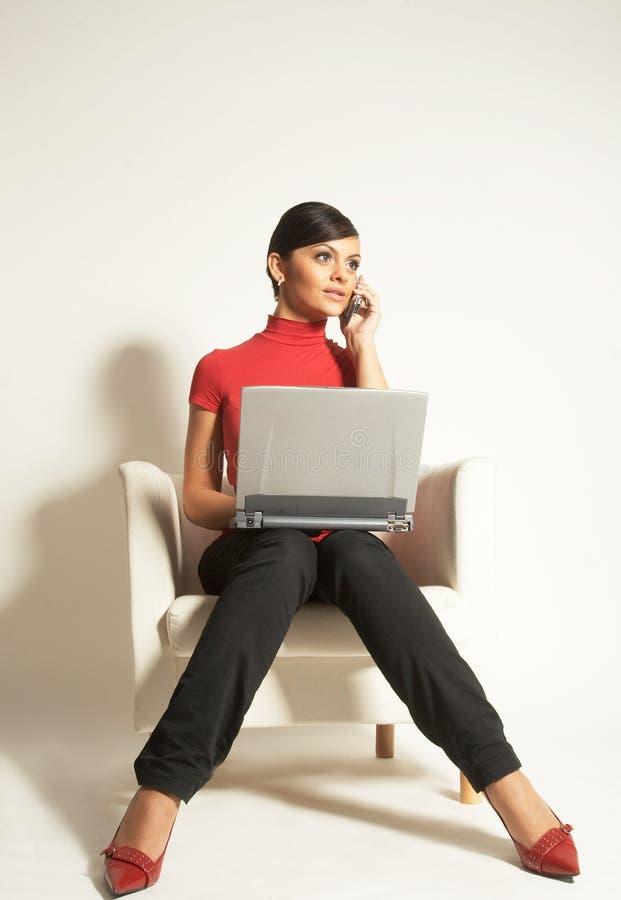 Femme d'affaires avec l'ordinateur portatif et le téléphone photo stock
