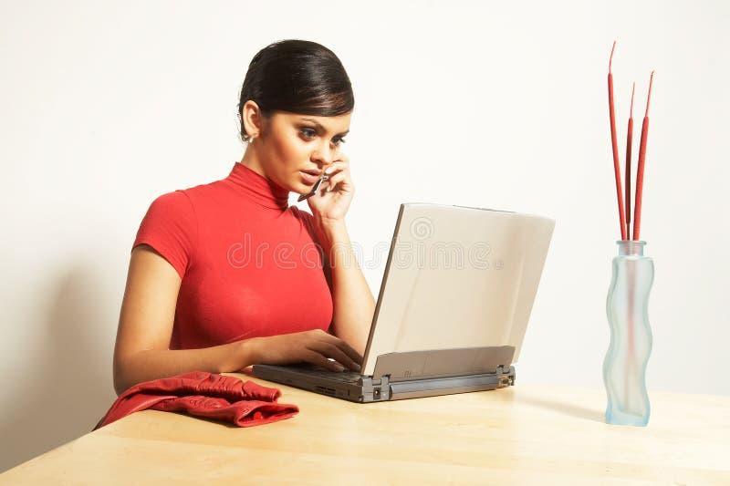 Femme d'affaires avec l'ordinateur portatif et le téléphone images stock