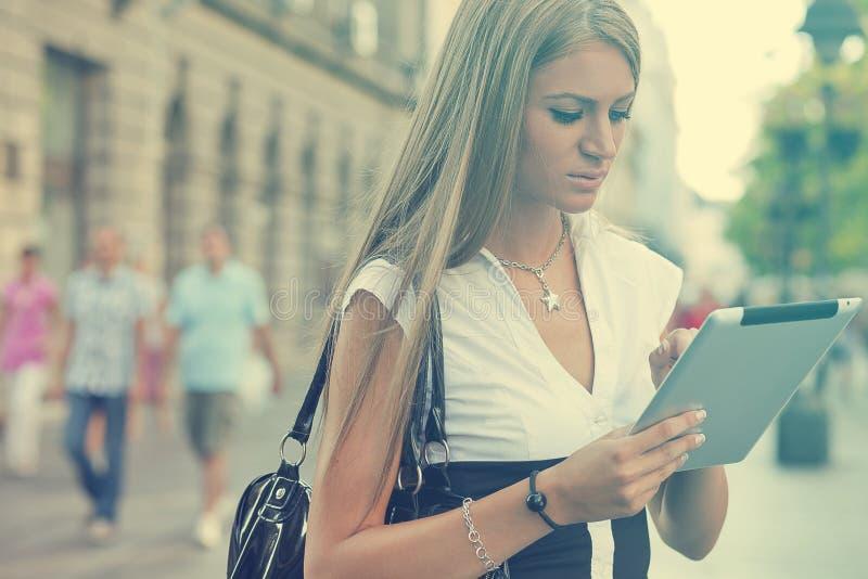 Femme d'affaires avec la tablette marchant sur la rue urbaine image libre de droits