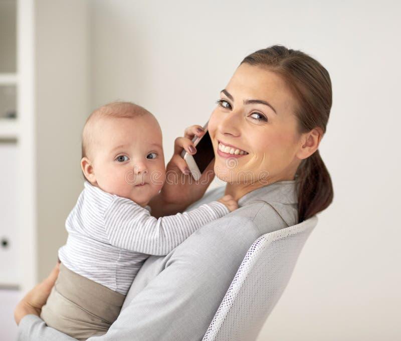 Femme d'affaires avec le bébé et smartphone au bureau images stock